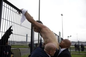 Xavier-Broseta-shirtless-tries-to-cross-a-fence-helped-by-security